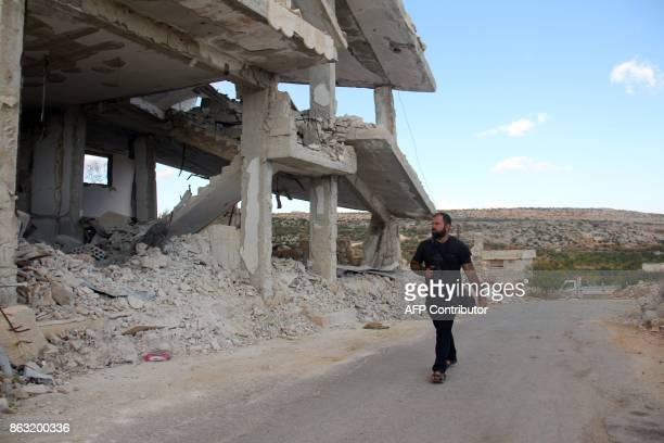 A picture taken on October 10 shows Syrian photographer Ahmed Khatib walking past damaged building in the village of Marayan in the Idlib province...