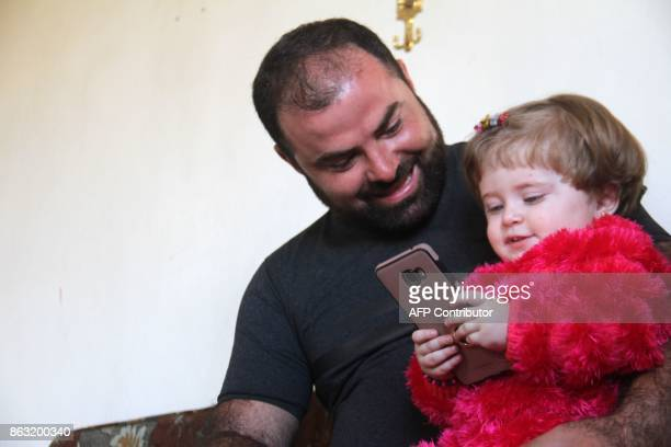A picture taken on October 10 shows Syrian photographer Ahmed Khatib sitting with his daughter Sara at their home in the village of Marayan in the...