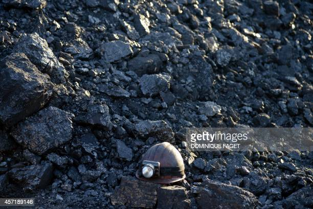Picture taken on October 12 2014 shows a miner helmet on a pile of coal at an illegal coal mine near Torez 60 kilometers east of Donetsk AFP PHOTO /...