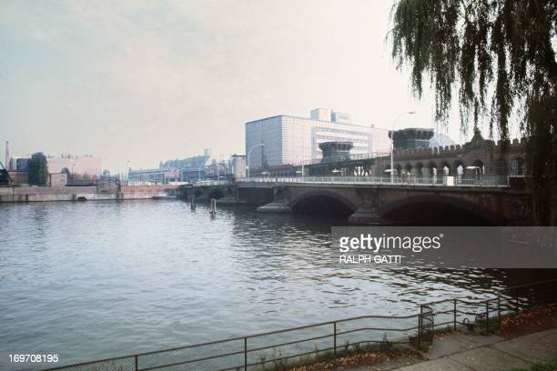 Picture taken on October 13 1976 of a watchtower on a bridge on the Spree river marking the border between East and West Berlin as a police boat is...