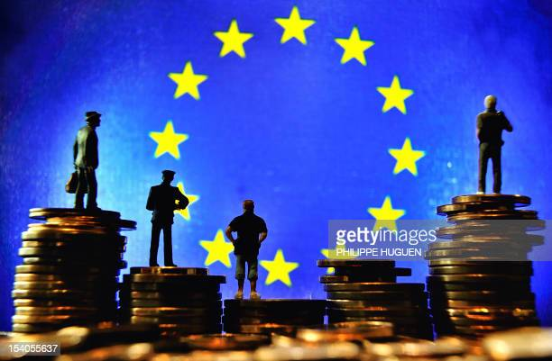 Picture taken on October 13 2012 in Lille shows an illustration made with figurines set up on Euro coins in front of the European Union flag AFP...