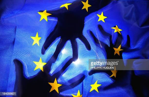 Picture taken on October 13 2012 in Lille shows an illustration showing the silhouette of hands behind a European Union flag AFP PHOTO / PHILIPPE...