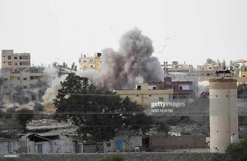 A picture taken on October 13, 2013 from Rafah in the southern Gaza Strip along the border with Egypt shows smoke rising from the Egyptian side following a controlled explosion at a smuggling tunnel dug beneath the border. Egypt's army has destroyed many of the tunnels on the Egyptian side of Rafah since July which are used to smuggle goods, including building material and fuel, into the blockaded Palestinian territory.
