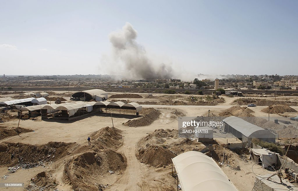 A picture taken on October 13, 2013 from Rafah in the southern Gaza Strip along the border with Egypt shows smoke rising from the Egyptian side following a controlled explosion at a smuggling tunnel dug beneath the border. Egypt's army has destroyed many of the tunnels on the Egyptian side of Rafah since July which are used to smuggle goods, including building material and fuel, into the blockaded Palestinian territory. AFP PHOTO/SAID KHATIB