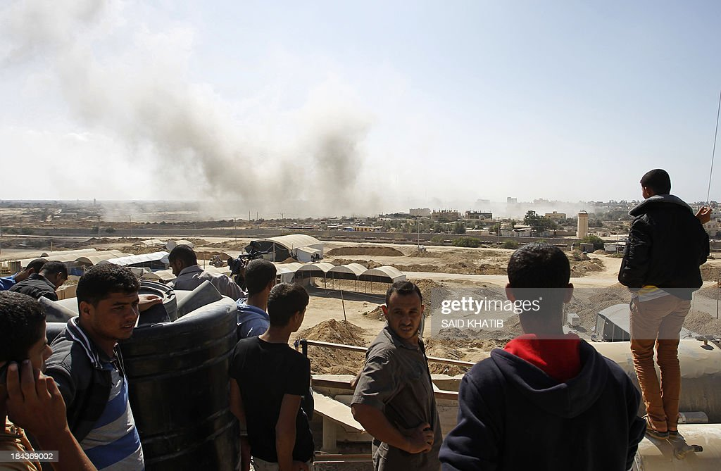 A picture taken on October 13, 2013 from Rafah in the southern Gaza Strip along the border with Egypt shows Palestinian men looking at smoke rising from the Egyptian side following a controlled explosion at a smuggling tunnel dug beneath the border. Egypt's army has destroyed many of the tunnels on the Egyptian side of Rafah since July which are used to smuggle goods, including building material and fuel, into the blockaded Palestinian territory.