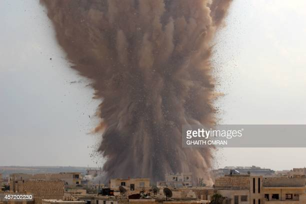 A picture taken on October 14 2014 shows a large explosion allegedly hitting a Syrian army military outpost in the southern part of the city of...