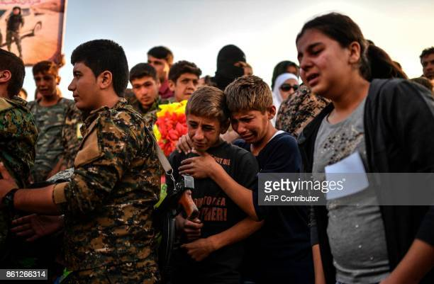 A picture taken on October 14 2017 in the Kurdish town of Kobane in northern Syria shows people and members of the Kurdish People's Protection Units...