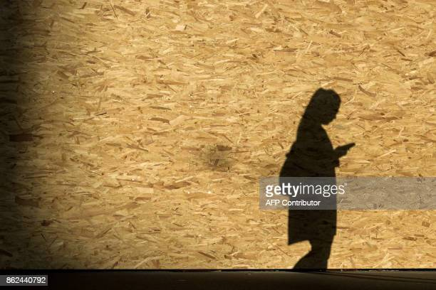 A picture taken on October 14 2017 shows on a wooden wall the shadow of a woman looking at ther mobile phone as she walks in Zurich / AFP PHOTO /...