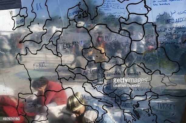 A picture taken on October 16 2015 shows migrants and refugees behind a map of Europe at the 'Moria' camp near the port of Mytilene on the Greek...