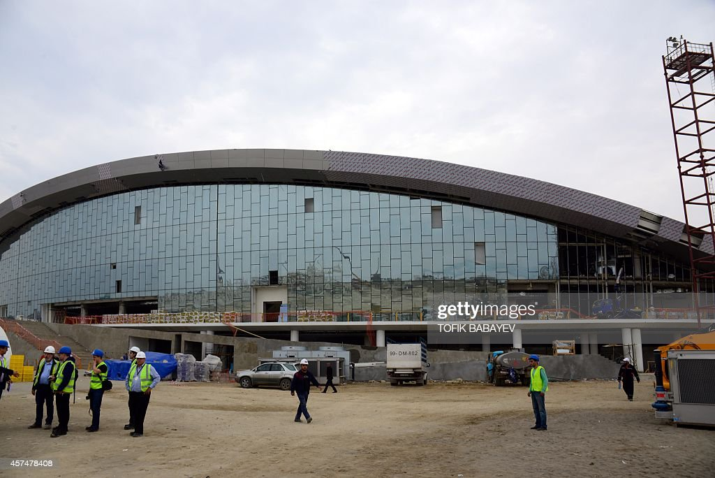 A picture taken on October 17 2014 shows employees standing in front of the swimming pool of the Aquatics Center in Baku The First European Games...