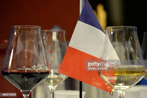 A picture taken on October 17 2015 shows a French flag between glasses of red and white wine on a table during the Blinded World Championships of...
