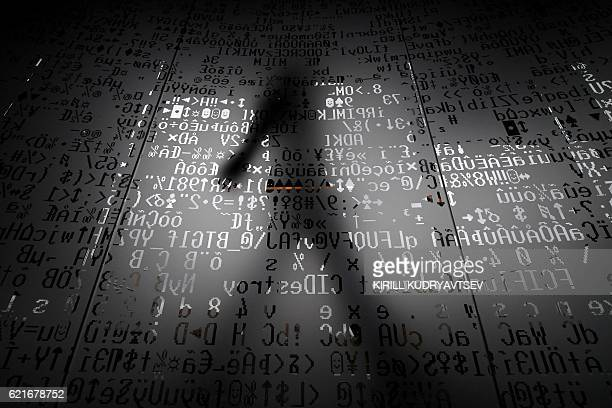 TOPSHOT A picture taken on October 17 2016 shows an employee walking behind a glass wall with machine coding symbols at the headquarters of Internet...