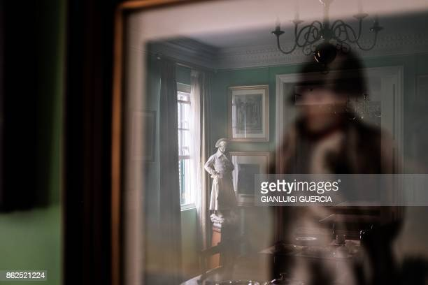A picture taken on October 17 2017 shows sculptures and paintings reflected in the Generals House room in the Napoleon House compound of his last...