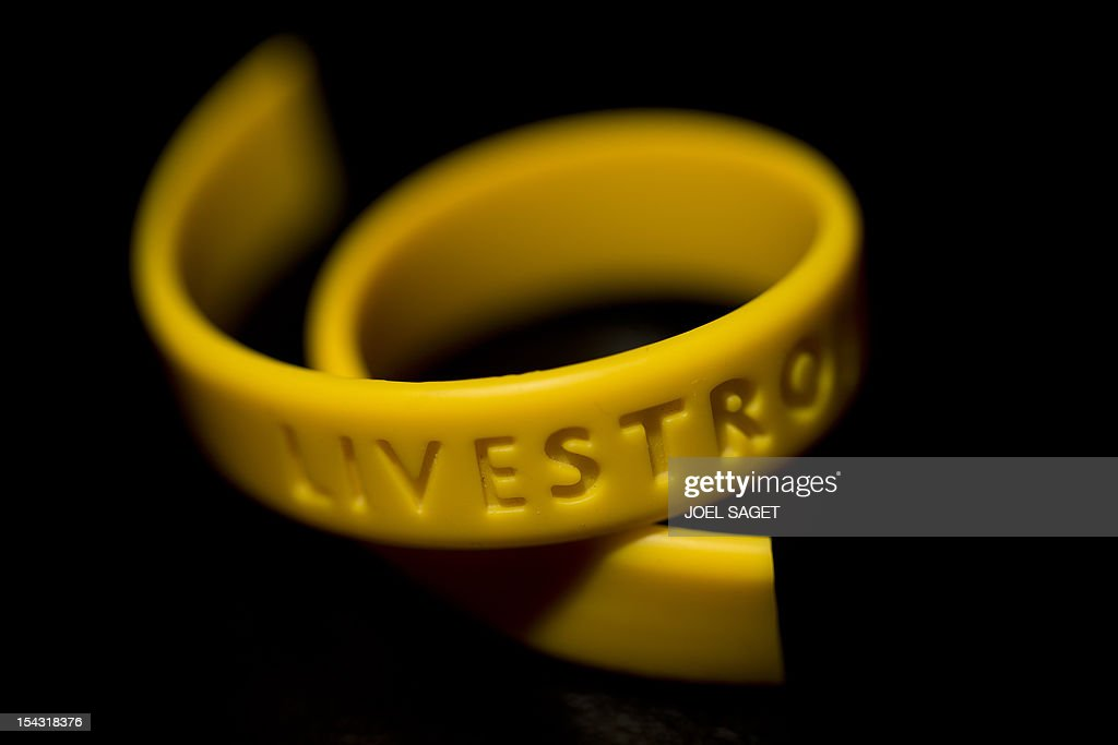 A picture taken on October 18, 2012 in Paris shows a broken Livestrong wristband, a yellow silicone gel bracelet launched as a fund-raising item for the Lance Armstrong Foundation. Lance Armstrong announced on October 17, 2012 he was stepping down as head of the foundation following the US Anti-Doping Agency (Usada) report published last week. AFP PHOTO/JOEL SAGET