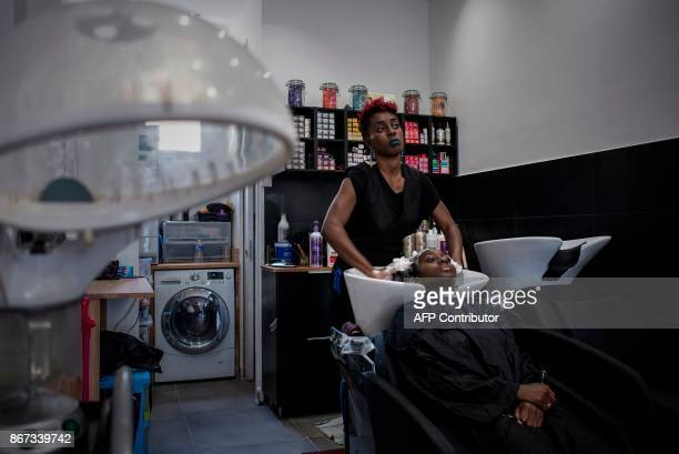 A picture taken on October 19 2017 shows a young customer getting a shampoo at a hairdressing salon specialized in afro natural hair care of in...
