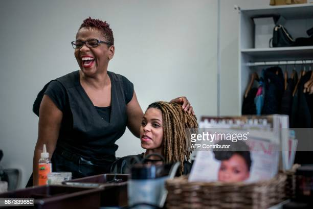 A picture taken on October 19 2017 shows Aline Tacite laughing as she takes care of a customer at her hairdressing salon in Bagneux 'The nappy' is a...