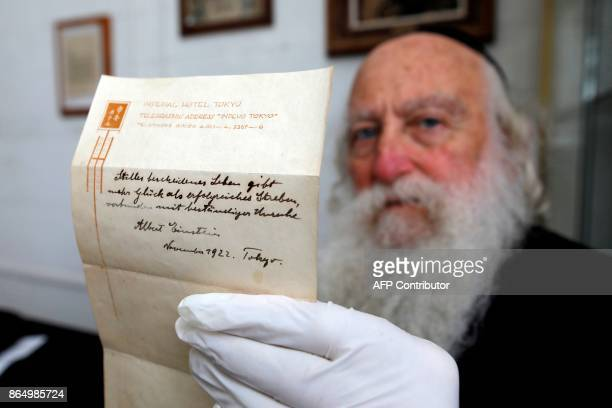 A picture taken on October 19 an UltraOrthodox Jewish man displaying one of two notes written by Albert Einstein in 1922 on hotel stationary from the...