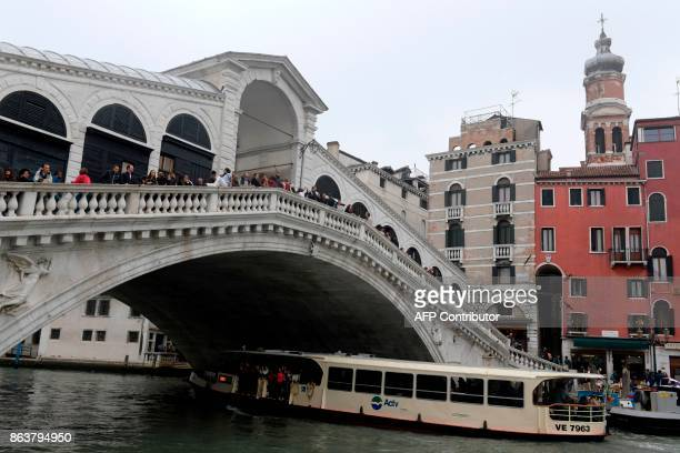 A picture taken on October 20 2017 in Venice shows a Vaporeto with tourists under the Rialto bridge at the Canal Grande A referendum will be held on...