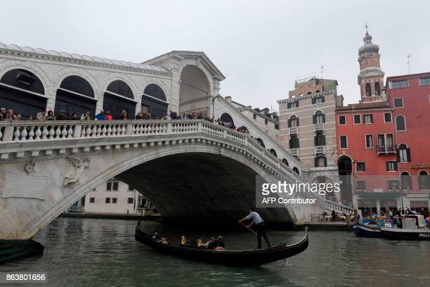 A picture taken on October 20 2017 shows a Gondola passing under the Rialto bridge at the Canal Grande A referendum will be held on October 22 2017...