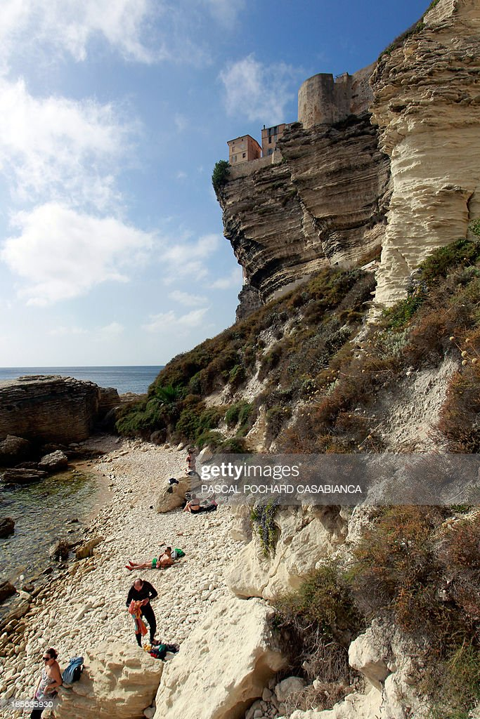 A picture taken on October 22, 2013 shows people on the beach of Bonifacio, France's southern Mediterranean island of Corsica. Bonifacio is classified as one of France's most beautiful villages.