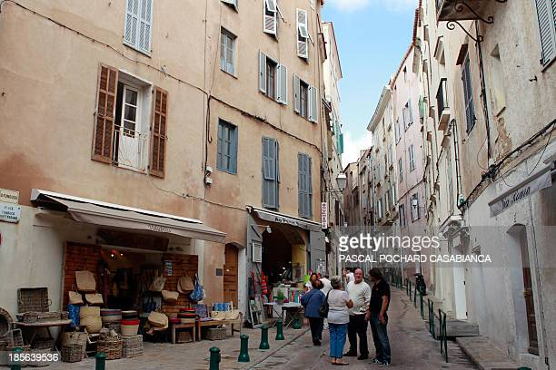 A picture taken on October 22 2013 shows tourists walking in a street of the old city of Bonifacio France's southern Mediterranean island of Corsica...