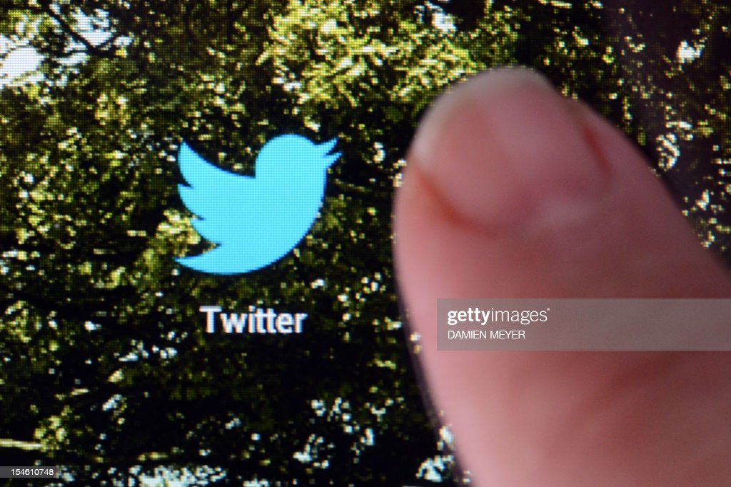 A picture taken on October 23, 2012 in Rennes, western France, shows a finger touching the screen of a handheld device that features a logo of the micro-blogging site Twitter.