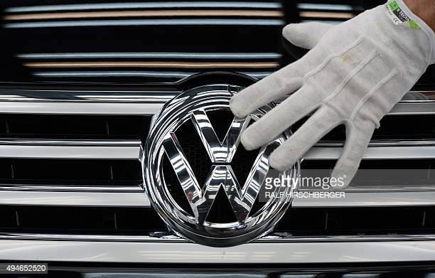 Picture taken on October 23 2015 shows an employee of German car maker Volkswagen touching the VW logo on a Phaeton car at the company's Glaeserne...