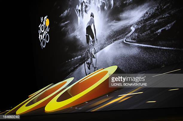 A picture taken on October 24 2012 in Paris shows a giant screen featuring a cyclist riding during a press conference to unveil the 2013 cycling...