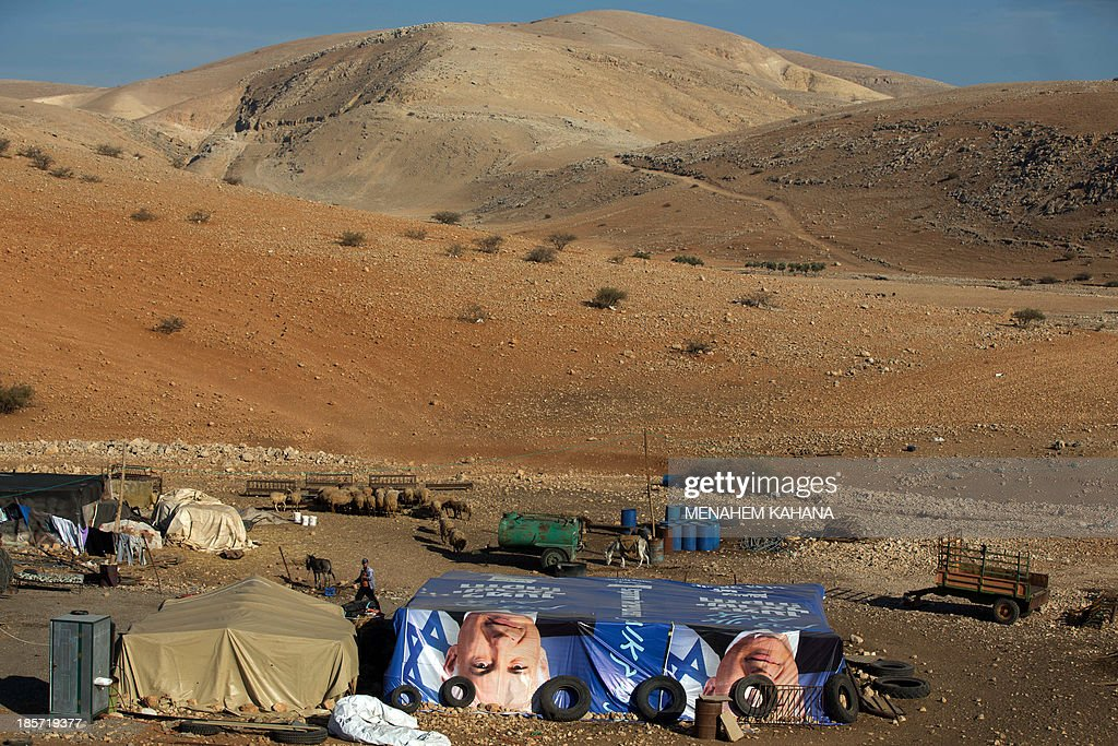 A picture taken on October 24, 2013 shows makeshifts tents covered with election posters depicting Israeli Prime Minister Benjamin Netanyahu at a West Bank Palestinian Bedouin camp in the Jordan valley. KAHANA