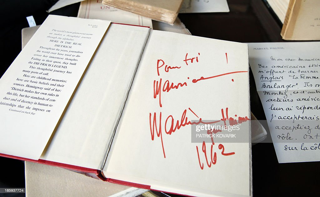 A picture taken on October 26, 2013 in Marnes-la-Coquette, outside Paris, shows an autograph on a book of late German singer and actress Marlene Dietrich offered to late French singer legend Maurice Chevalier, displayed in Chevalier' s house, 'La Louque'. 41 years after his death, furniture, souvenirs and home of Maurice Chevalier will be auctionned December 9, 2013, in Paris, following the death of the singer's companion, Odette Meslier, last May.