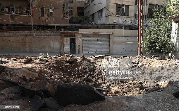 A picture taken on October 26 2016 shows a hole in the ground following reported government shelling a night earlier on the rebelheld town of Douma...