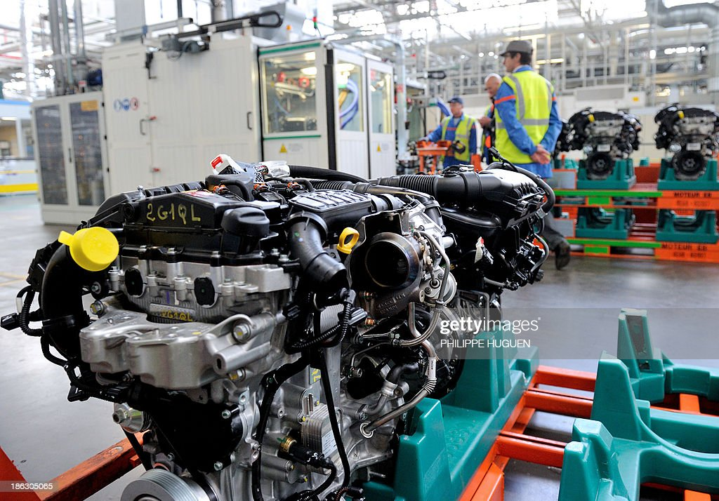 A picture taken on October 29, 2013 shows French carmaker PSA Peugeot Citroen's new engine, the three-cylinder EB Turbo 'Pure Tech' at an assembly line in the Francaise de Mecanique plant in Douvrin, northern France.
