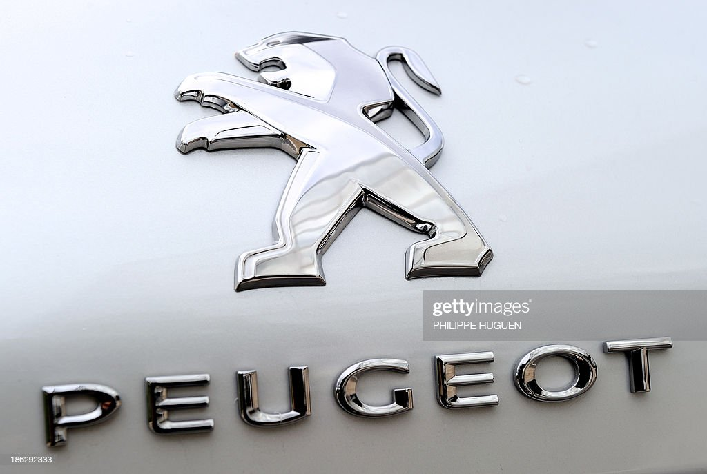 A picture taken on October 29, 2013 shows the logo of a new Peugeot 308 equipped with French carmaker PSA Peugeot Citroen's new engine, the three-cylinder EB Turbo 'Pure Tech', on display during the inauguration of an assembly line producing PSA's engine at the Francaise de Mecanique plant in Douvrin, northern France.