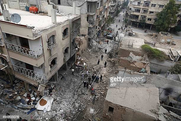 A picture taken on October 29 2015 shows Syrians inspecting damaged buildings following a reported air strike by Syrian government forces in the...
