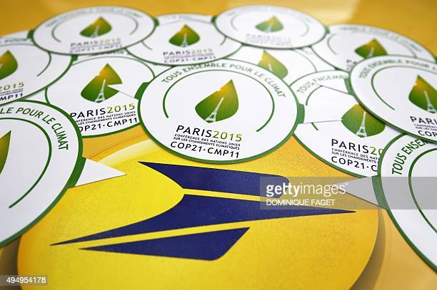 A picture taken on October 30 2015 shows stickers of the COP21 and the logo of the French postal service 'La Poste' in Paris ahead of the Climate...