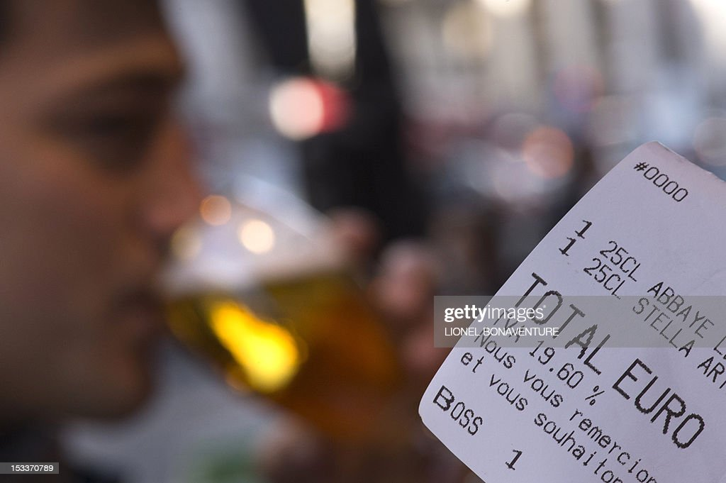 A picture taken on October 4, 2012 in a cafe in Paris shows a bill with the 19.60 percent VAT rate while a person (background) is drinking a glass of beer. French bar and cafe keepers either feel resignation or anger after the French government announced on October 1 that the level of taxation of beer will increase in France, which is expected to generate 480 millions of euros to French public welfare system (Securite sociale). AFP PHOTO / LIONEL BONAVENTURE