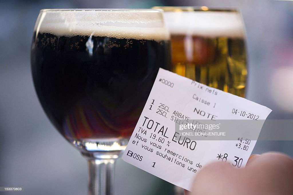 A picture taken on October 4, 2012 in a cafe in Paris shows a bill with the 19.60 percent VAT rate beside glasses of beer. French bar and cafe keepers either feel resignation or anger after the French government announced on October 1 that the level of taxation of beer will increase in France, which is expected to generate 480 millions of euros to French public welfare system (Securite sociale). AFP PHOTO / LIONEL BONAVENTURE