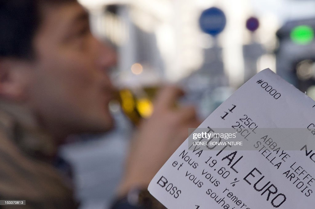 A picture taken on October 4, 2012 in a cafe in Paris shows a bill with the 19.60 percent VAT rate while a person (background) is drinking a glass of beer. French bar and cafe keepers either feel resignation or anger after the French government announced on October 1 that the level of taxation of beer will increase in France, which is expected to generate 480 millions of euros to French public welfare system (Securite sociale).