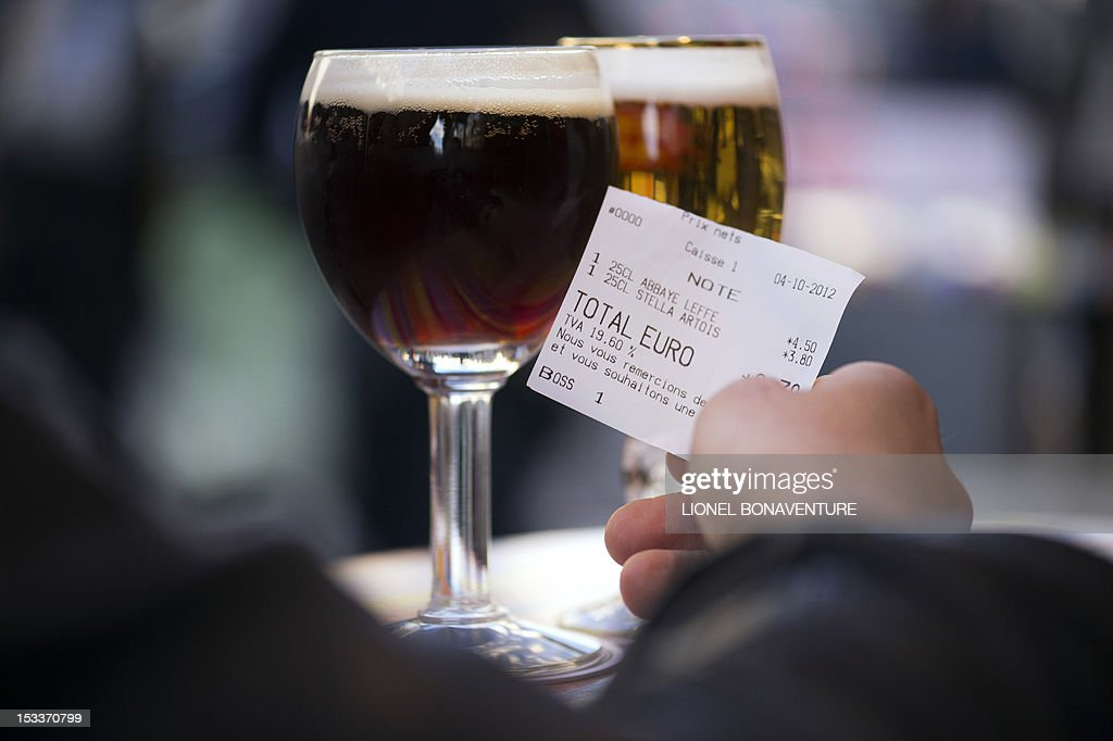 A picture taken on October 4, 2012 in a cafe in Paris shows a person holding a bill beside glasses of beer. French bar and cafe keepers either feel resignation or anger after the French government announced on October 1 that the level of taxation of beer will increase in France, which is expected to generate 480 millions of euros to French public welfare system (Securite sociale).