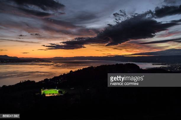 A picture taken on October 5 from the Mont de Gourze in Riez western Switzerland shows a football pitch illuminated with floodlights at sunset above...