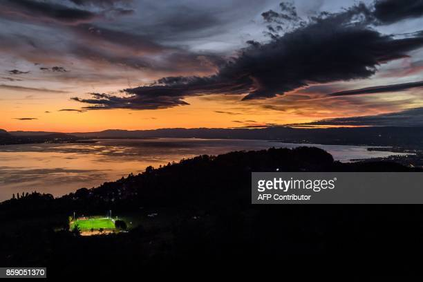 TOPSHOT A picture taken on October 5 from the Mont de Gourze in Riez western Switzerland shows a football pitch illuminated with floodlights at...