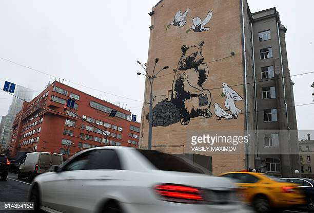 TOPSHOT A picture taken on October 7 2016 show cars driving past a bulding with a graffiti showing a brown bear distributing bulletproof vests to...