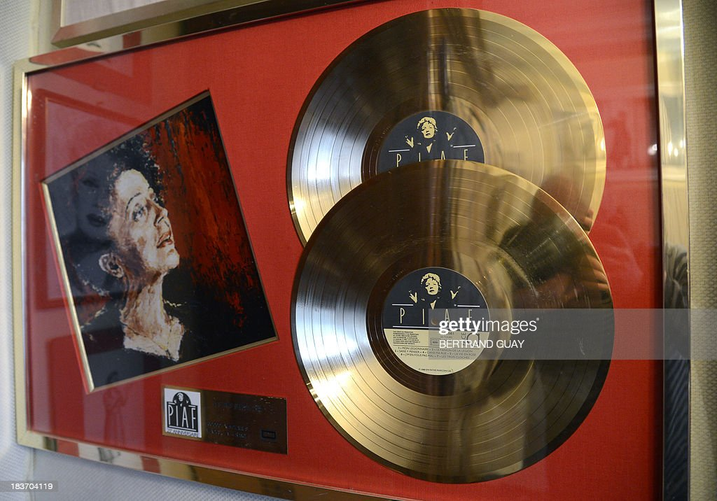 A picture taken on October 9, 2013 shows a painting representing late French singer Edith Piaf displayed next to records in her apartment now turned into a museum in Paris, on the eve of commemorating the 50th anniversary of her death. France's greatest global star Edith Piaf died fifty years ago on October 10, 1963.