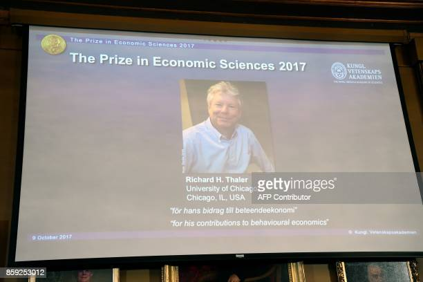 A picture taken on October 9 2017 in Stockholm shows a giant screen bearing a portrait of US economist Richard Thaler after the Nobel Committee...
