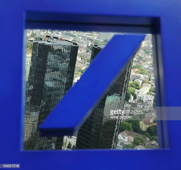 Picture taken on on August 18 2010 shows the headquarters towers of German bank Deutsche Bank reflect in the bank's logo seen in Frankfurt/M western...