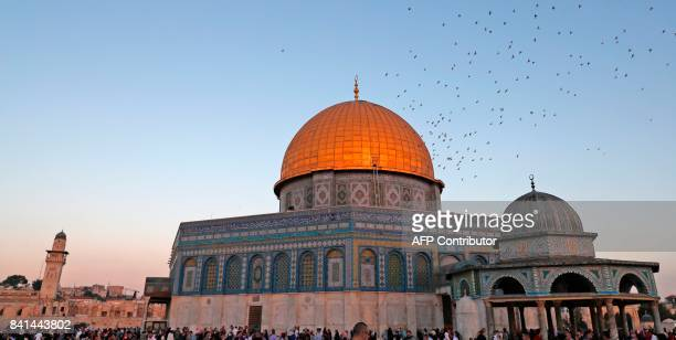 A picture taken on September 1 2017 shows birds flying past the Dome of Rock mosque inside the AlAqsa Mosque compound Islam's third holiest site as...