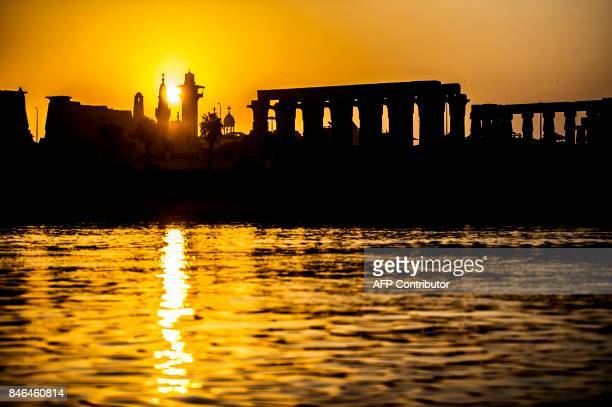 TOPSHOT A picture taken on September 10 2017 shows a silhouette of the skyline of the southern Egyptian city of Luxor at sunrise showing the pylons...