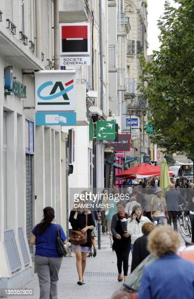 A picture taken on September 12 2011 shows people walking under the logos of French banks Societe Generale Credit Agricole and BNP Paribas in Rennes...