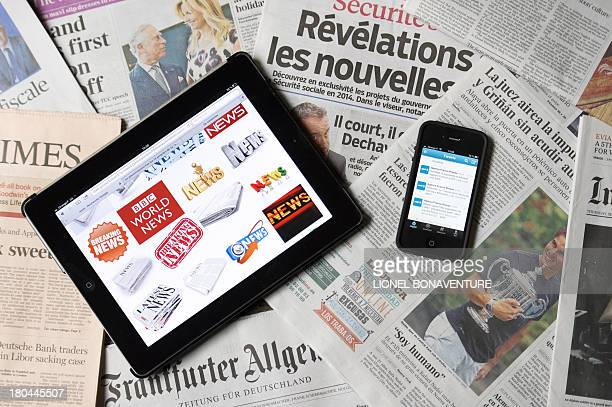 A picture taken on September 12 2013 in Paris shows a tablet and a smartphone connected on news websites and world newspapers AFP PHOTO / LIONEL...