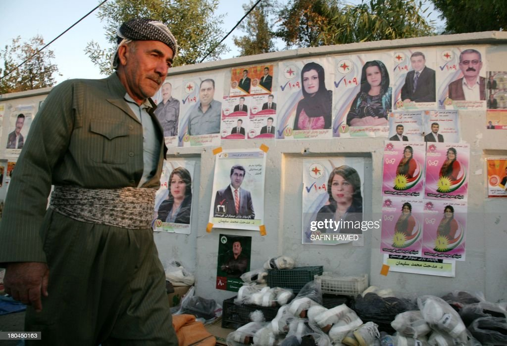 A picture taken on September 12, 2013 shows an Iraqi Kurdish man walking past electoral campaign posters of candidates running in the Kurdistan parliament election, in the northern Iraqi city of Arbil. The election is to be held on September 21, in the Iraq's autonomous Kurdish region. AFP PHOTO/SAFIN HAMED